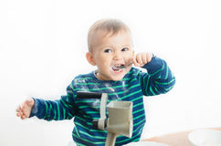 Baby sugar grinder. The child with a spoon eating sugar Royalty Free Stock Photography