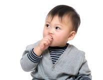Baby suger hans finger Arkivfoto