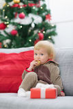 Baby in suit of Santa's helper with Christmas gift Stock Image