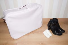 Baby suitcase, bootees and woman shoes Stock Photography