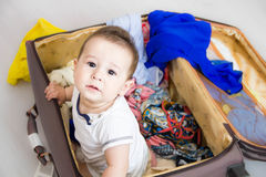 Baby in a suitcase, a journey. A small child got out of the suitcase and looks at you. Packed for vacation in sea resort. The chil Royalty Free Stock Photo