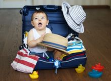 Baby in suitcase ready for travel. Cute baby boy sitting in the suitcase with hat in his hands, packed for vacation full of clothes. Traveling with baby Royalty Free Stock Images