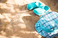 Baby summer beachwear, flip flops, hat on sand beach royalty free stock photo