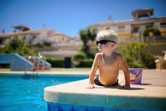 Baby summer by the pool basking in the sun. Kid in sunglasses lying on his stomach near the pool Royalty Free Stock Images