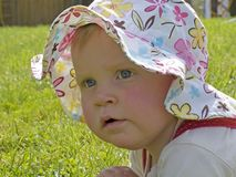 Baby with sun hat. On a meadow Royalty Free Stock Image