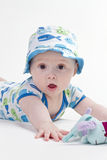 Baby in sun hat. Bright eyed baby boy in decorated top and matching sun hat lying on his front reaching for a soft toy royalty free stock photo