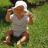 Baby with sun hat. Little baby boy with sun hat in the meadow stock image