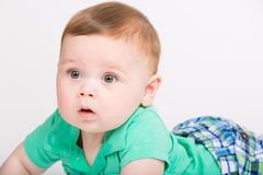 Baby Surprised Close Up. 8 month year old baby lays on his stomach looking to the left surprised expression. dressed in a cute green polo shirt and blue plaid Royalty Free Stock Photography
