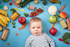 Baby surrounded with fruits and vegetables Stock Images