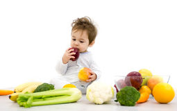 Baby surrounded with fruits and vegetables, healthy child nutrition Stock Image