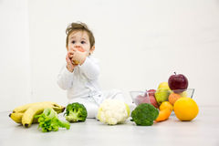 Baby surrounded with fruits and vegetables, healthy child nutrition Royalty Free Stock Image