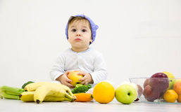 Baby surrounded with fruits and vegetables, healthy child nutrition Stock Photos