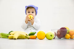Baby surrounded with fruits and vegetables, healthy child nutrition Royalty Free Stock Images