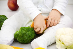 Baby surrounded with fruits and vegetables on yellow blanket, healthy child nutrition first food of the child Royalty Free Stock Images