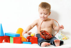 Baby, surrounded by toys Stock Photos