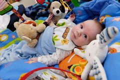Baby surrounded by toys Royalty Free Stock Image