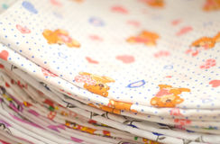 Baby swaddling with bears and hearts. Heap of folded linen of various colors. Pile of the washed and ironed linen. Royalty Free Stock Photos
