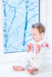 Baby in sweater with snowflake next to window Stock Photos