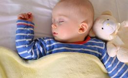 Baby is sweetly sleeping with his teddy bear Stock Images