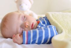 Baby is sweetly sleeping with his teddy bear Stock Image