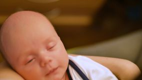 Baby sweetly sleeps in the arms of her mother. Newborn smiles in a dream. Rear view over the shoulder stock video
