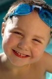 Baby swimmer. Happy toddler in diving goggles standing in the pool; tight headshot Royalty Free Stock Image
