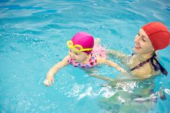 Baby swimming. One year  baby girl at his first swimming lesson with mother Royalty Free Stock Images