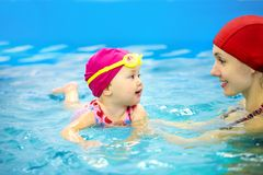 Baby swimming. One year  baby girl at his first swimming lesson with mother Royalty Free Stock Photo