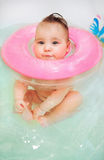 Baby swimming in bath with neck swim ring. Baby with neck swim ring in the bath Royalty Free Stock Image