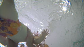 Baby is swimming in the child pool: underwater. The camera is under the water in the child pool. The father holding his baby on the hands. Young man bathing his stock footage