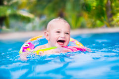 Baby in a swimming pool. Adorable little baby boy having fun in a swimming pool in a beautiful tropical resort learning to swim playing with colofrul inflatable royalty free stock photography