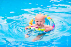 Baby in a swimming pool. Adorable little baby boy having fun in a swimming pool in a beautiful tropical resort learning to swim playing with colofrul inflatable stock images