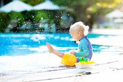 Baby in swimming pool. Family summer vacation. Baby with toy boat in swimming pool. Little boy learning to swim in outdoor pool of tropical resort. Swimming Royalty Free Stock Photo