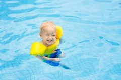 Baby in swimming pool. Kids swim. Baby with inflatable armbands in swimming pool. Little boy learning to swim in outdoor pool of tropical resort. Swimming with royalty free stock photo