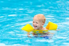 Baby in swimming pool. Kids swim. Baby with inflatable armbands in swimming pool. Little boy learning to swim in outdoor pool of tropical resort. Swimming with stock images