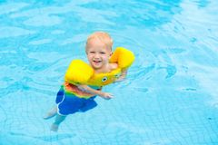 Baby in swimming pool. Kids swim. Baby with inflatable armbands in swimming pool. Little boy learning to swim in outdoor pool of tropical resort. Swimming with stock photos