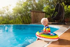 Baby in swimming pool. Kids swim. Child summer fun. Baby in swimming pool. Little boy playing in outdoor pool. Kids learn to swim. Child with inflatable toy royalty free stock photography