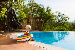 Baby in swimming pool. Kids swim. Child summer fun. Baby in swimming pool. Little boy playing in outdoor pool. Kids learn to swim. Child with inflatable toy Royalty Free Stock Images