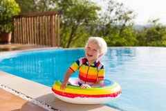 Baby in swimming pool. Kids swim. Child summer fun. Baby in swimming pool. Little boy playing in outdoor pool. Kids learn to swim. Child with inflatable toy Royalty Free Stock Photo