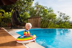 Baby in swimming pool. Kids swim. Child summer fun. Baby in swimming pool. Little boy playing in outdoor pool. Kids learn to swim. Child with inflatable toy Stock Photos