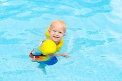 Baby in swimming pool. Kids swim. Baby with inflatable armbands in swimming pool. Little boy learning to swim in outdoor pool of tropical resort. Swimming with royalty free stock images