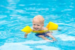 Baby in swimming pool. Kids swim. Baby with inflatable armbands in swimming pool. Little boy learning to swim in outdoor pool of tropical resort. Swimming with stock image