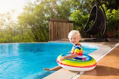 Baby in swimming pool. Kids swim. Child summer fun. Baby in swimming pool. Little boy playing in outdoor pool. Kids learn to swim. Child with inflatable toy Royalty Free Stock Photos