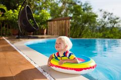 Baby in swimming pool. Kids swim. Child summer fun. Baby in swimming pool. Little boy playing in outdoor pool. Kids learn to swim. Child with inflatable toy Stock Image