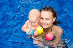 Baby in the swimming pool. Mom teaches the child to swim in the swimming pool Stock Photo