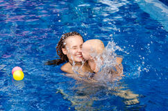 Baby in the swimming pool. Mother and baby play with ball in the swimming pool stock photography
