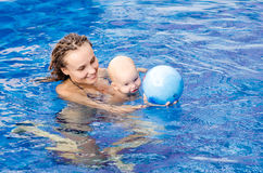 Baby in the swimming pool. Mother and baby play with ball in the swimming pool Stock Photo