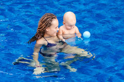 Baby in the swimming pool. Mother and baby play with ball in the swimming pool Royalty Free Stock Photos