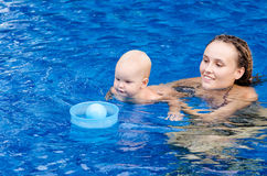 Baby in the swimming pool. Mother and baby play with ball in the swimming pool Royalty Free Stock Images