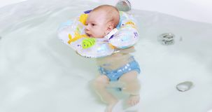 Baby swims in the bathroom. Baby boy swims in a white bathtub in a life preserver stock video